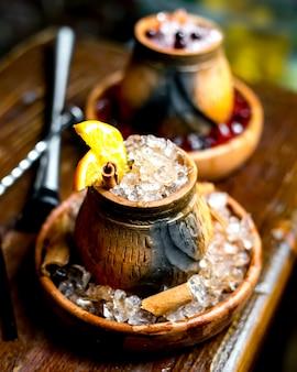 Деревянный бокал с ледяной имбирной палочкой и долькой апельсина