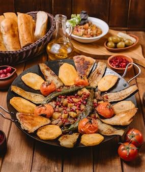 Азербайджанский сайджиз, приготовленный с баклажаном, картофелем, помидорами и перцем в чугунной сковороде