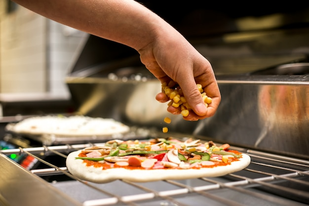 Шеф-повар кладет кукурузу на тесто для пиццы, покрытое томатным соусом