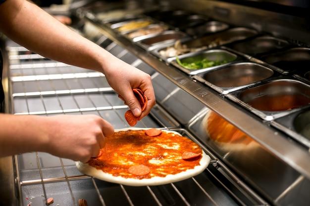 Шеф-повар кладет пепперони на тесто для пиццы, покрытое томатным соусом