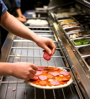 シェフがトマトソースで覆われたピザ生地にソーセージを置く