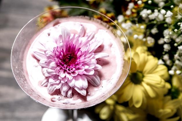 マティーニグラスの上に花とカクテルのクローズアップ