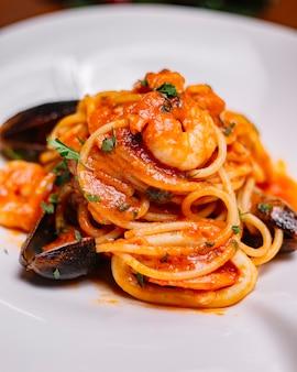 ムール貝のエビのトマトソースとパセリのシーフードスパゲッティのクローズアップ
