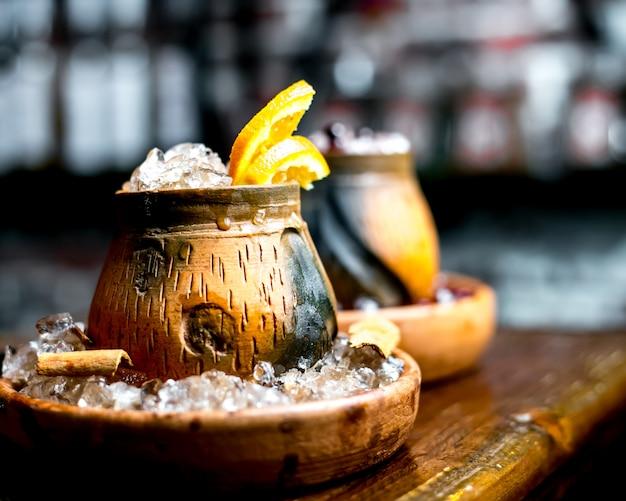 Закройте вверх деревянного стекла напитка с ручкой имбиря льда и ломтиком апельсина