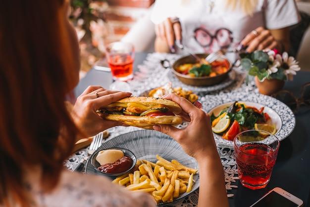 Крупным планом женщина, держащая куриный сэндвич, подается с картофелем фри и соусами