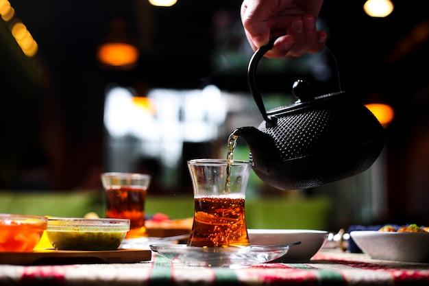 Мужчина наливает чай в стакан армуду из каменного чайника