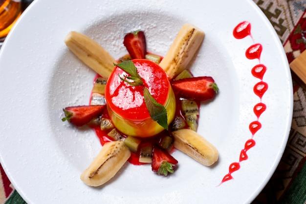 Сверху крупным планом десертная тарелка, украшенная клубничным сиропом, кусочками бананового киви и кусочками клубники