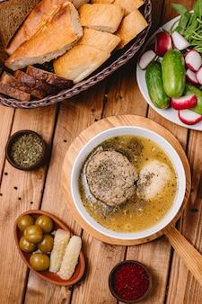 Вид сверху супа фрикадельки азербайджанской кофты, украшенный высушенными листьями мяты