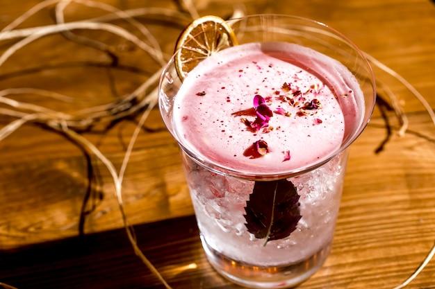 Вид сверху розовый коктейль украшенный сушеными лепестками роз