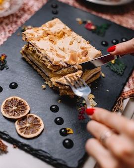 Женщина режет слоеный малиновый торт с кремом и малиновым вареньем с фисташками