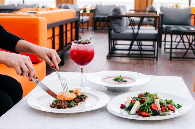 茶色の麺のベリーサラダスープとカクテルとサーモンと昼食の女性