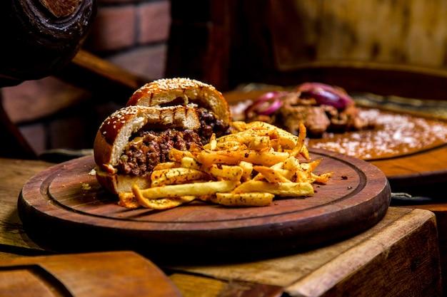 Мясной бургер, картофель фри со специями, вид сбоку