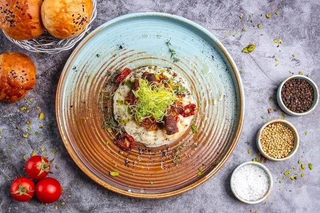 Вид сверху жареного мяса, помещенного на картофельное пюре, украшенное тертым болгарским перцем и тимьяном