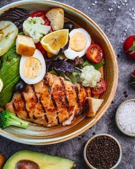グリルチキンブロッコリーカリフラワートマトレタスアボカドとレタスのヘルシーダイエットサラダのトップビュー
