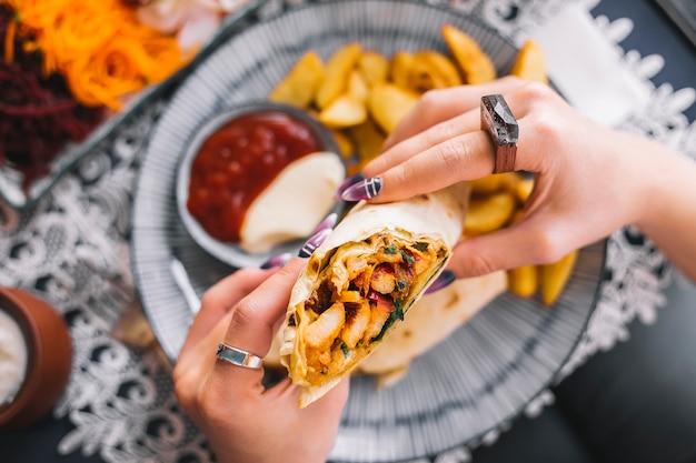 Женщина держит куриное буррито с картофелем фри и соусами