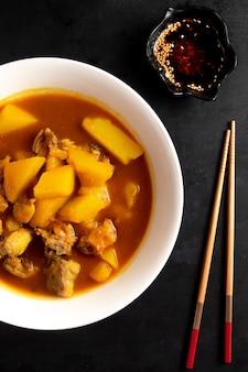 Вид сбоку китайский суп с курицей и картофелем в тарелке