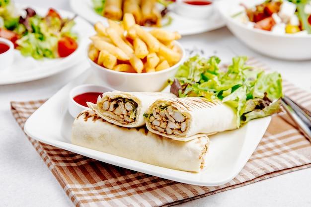 Вид сбоку куриного донера с салатом грен и картофелем фри