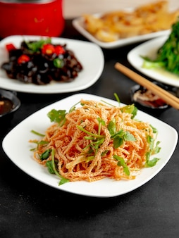 Вид сбоку тофу с кориандром в тарелке