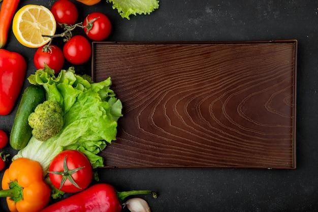 Вид сверху овощей, как брокколи, салат, помидор, огурец с лимоном и разделочная доска на черном фоне