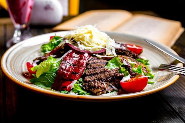 Вид спереди на гриле мясо с овощами и листьями салата с тертым сыром на тарелке
