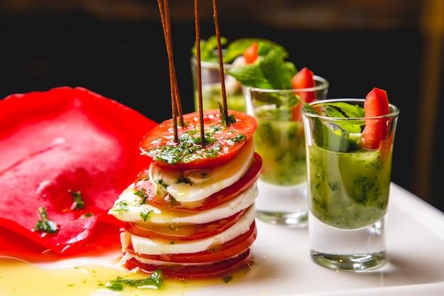 Вид спереди салат-каприз с соусом песто в три выстрела на тарелке