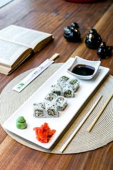 醤油生姜とわさびの皿と本のテーブルの上で巻き寿司の側面図
