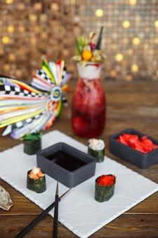 Тарелка суши гункан с соевым соусом и имбирем