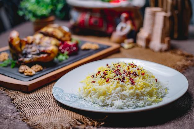 Вареный рис со специями на белой тарелке на столе