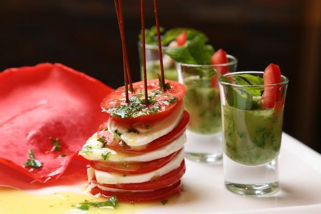 トマトのモッツァレラチーズとバジルの白い正方形プレートのカプレーゼサラダ串
