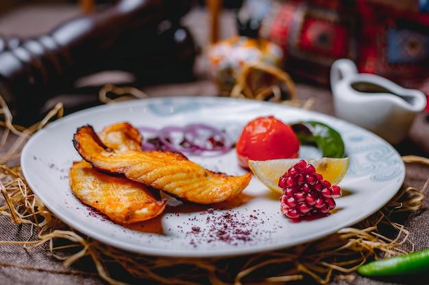 Лосось на гриле подается с лимоном, помидорами, зеленым острым перцем, гранатом, электронной фасолью и красным луком с пряностями на белой тарелке