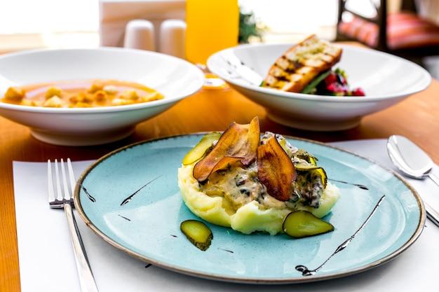 Картофельное пюре с жареными баклажанами, солеными огурцами и сливочным соусом на тарелке