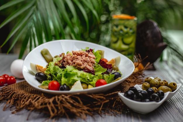 Салат из тунца с помидорами черри и оливками в белой тарелке
