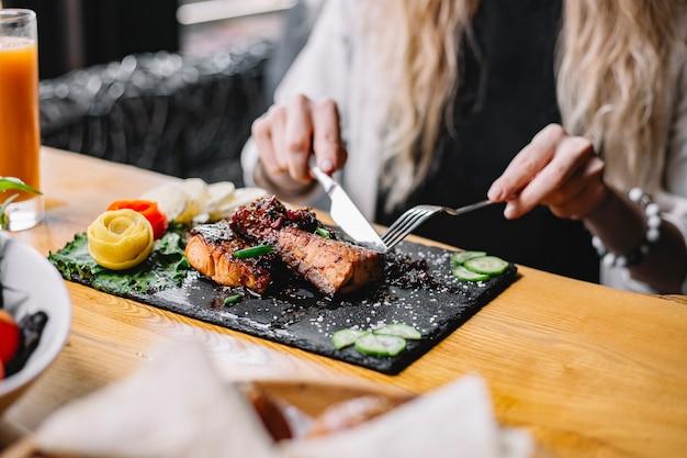 テーブルでハーブと野菜の焼き魚の切り身を食べる女性