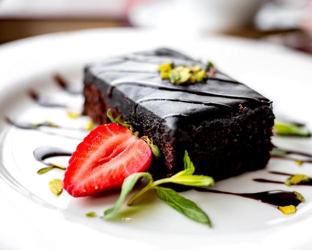 Вид сбоку шоколадный торт украшен клубникой на тарелке