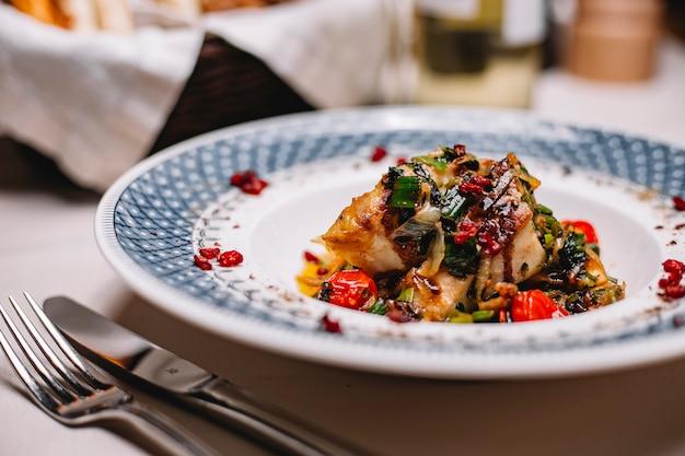 Вид сбоку рыбного филе на гриле с овощами, подается со свежей зеленью и соусом на тарелке