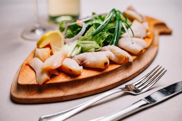 Вид сбоку нарезанной рыбы ассорти из копченой сельди со свежей зеленью зеленого лука и лимона на деревянной тарелке