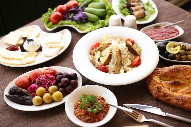 Вид сбоку на сервированный стол с различными блюдами, салат цезарь, маринованные овощи, сырная тарелка и свежие овощи