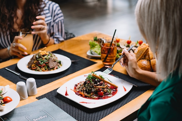 テーブルでオリーブオイルを添えて新鮮な野菜サラダを食べる女性の側面図