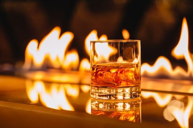 燃える炎の背景に氷とウイスキーのガラスの側面図