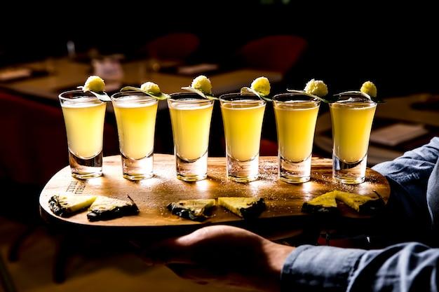 Вид сбоку набора алкогольных коктейлей в рюмки с кусочками ананаса на деревянной доске на темном фоне