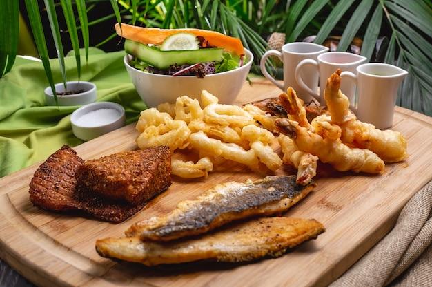 Морепродукты на гриле на деревянной доске рыбные креветки кальмаровый зеленый салат, вид сбоку