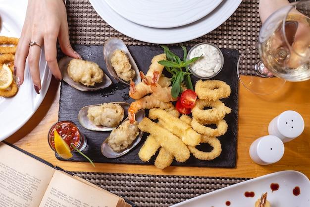 Тарелка с морепродуктами каламарские креветки мидии лимонный соус тар-тар томатная мята вид сверху