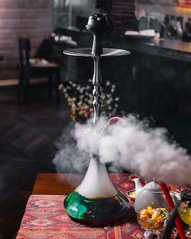 Зеленый дымящийся кальян на столе, вид сбоку