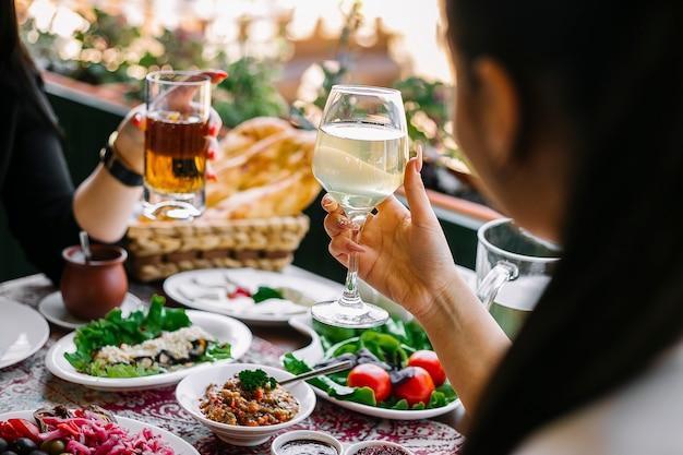 さまざまな料理のテーブルでレモネードのグラスを保持している女性