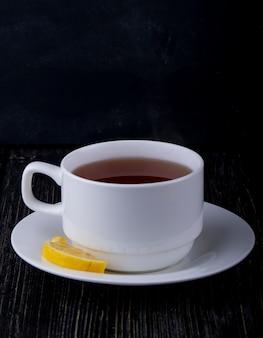Вид сбоку чашки чая с ломтиком лимона на черном
