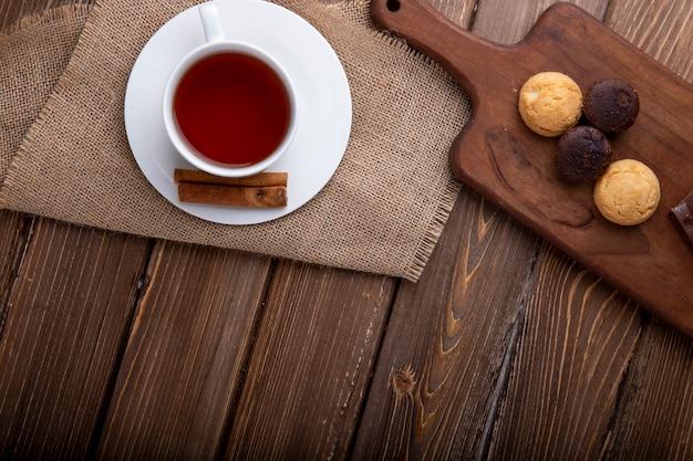 Вид сверху печенье на деревянной разделочной доске с чашкой чая на деревенском