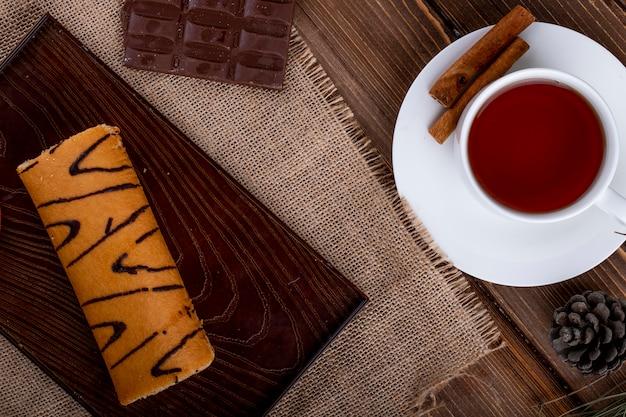 Вид сверху рулет с абрикосовым джемом на деревянной доске подается с чашкой чая на деревенском