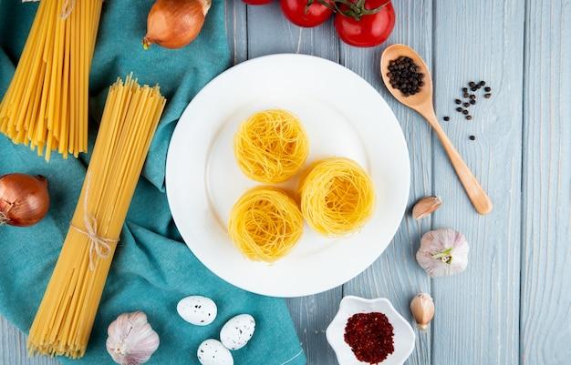 Паста тальолини на белой тарелке спагетти с яйцами и чесноком лук вид сверху