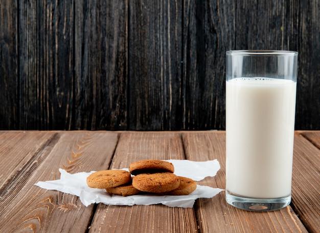 Вид спереди овсяные печенья на кальке со стаканом молока на деревянном фоне