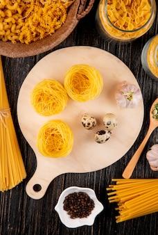 Итальянская паста тальолини с яйцами, чесноком, фарфалини, спагетти, сухие травы, вид сверху